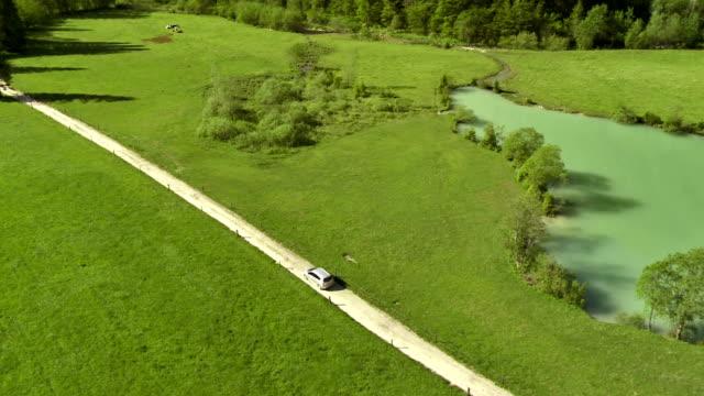 WS Luftaufnahme Auto auf der Schotterstraße umgeben von Weiden