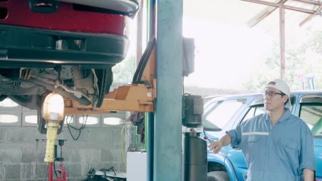 自動車修理店で車のジャックに車、ゆっくりとそれを取る。 - コショウ点の映像素材/bロール