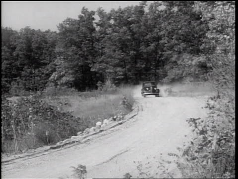 stockvideo's en b-roll-footage met b/w 1938 car on country road raising dust cloud driving past camera - 1938
