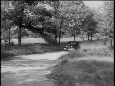 stockvideo's en b-roll-footage met b/w 1938 pan car on country road raising dust cloud driving toward camera - 1938