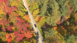 AERIAL: SUV car on leaf peeping road trip driving through colorful autumn forest