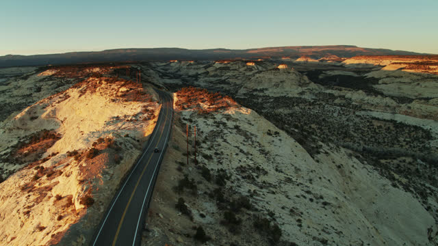 auto auf lonely desert road bei sonnenaufgang - aerial - grand staircase escalante national monument stock-videos und b-roll-filmmaterial