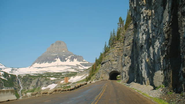 Car POV on narrow mountain road through a tunnel in Glacier National Park, Montana.