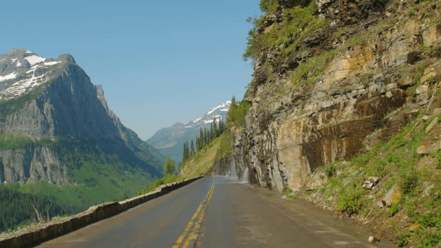 car pov on narrow road through glacier national park and past the weeping wall where water splashes over the canyon wall and onto the road. - glacier national park us stock videos and b-roll footage