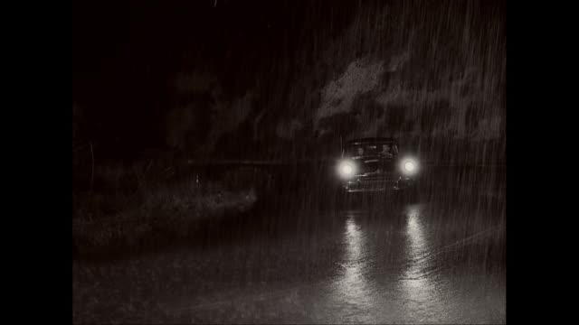 WS PAN Car on road during rain season at night / United States