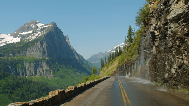 Car POV on road with water flowing down the Weeping Wall and onto a mountain pass in Glacier National Park, Montana.