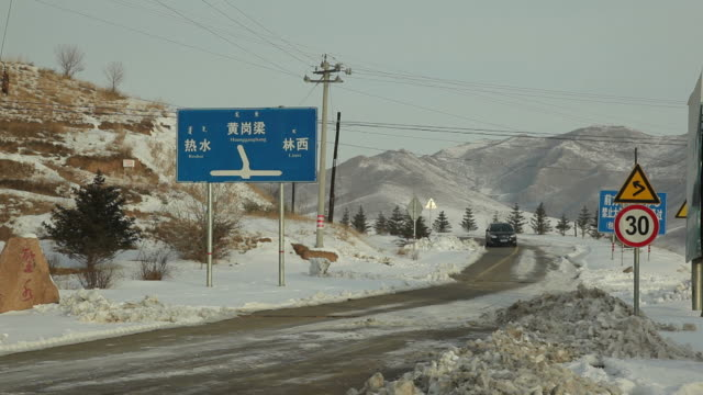 ws car on snowy road / inner mongolia, china - segnaletica stradale video stock e b–roll