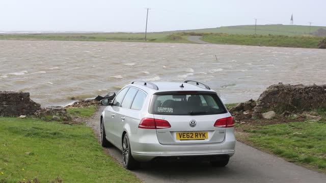 car on south walney cut off by storm surge flooding, walney island, cumbria, uk. - tide stock videos & royalty-free footage