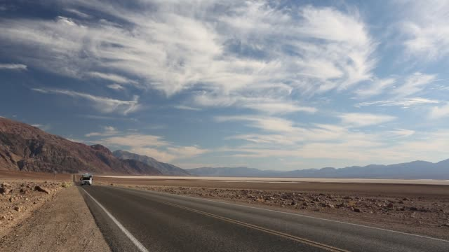 a car on the road near badwater which is the lowest point in the usa being 282 feet below sea level in death valley. death valley is the lowest, hottest, driest place in the usa, with an average annual rainfall of around 2 inches, some years it does not re - camper van stock videos & royalty-free footage