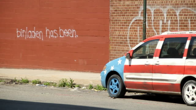 Car painted with stars and stripes is parking in front of a wall