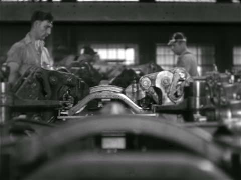 vidéos et rushes de b/w 1936 car parts moving on conveyor belt towards camera as men work on them in chevrolet factory - chaîne de production
