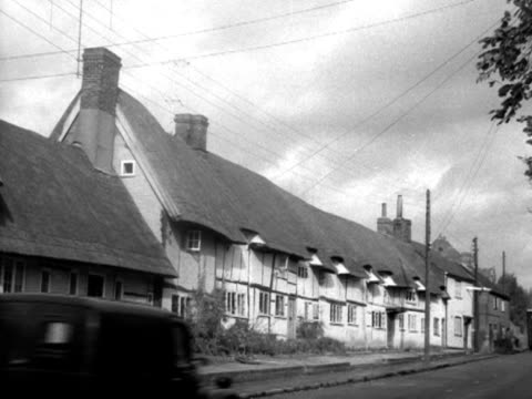 a car passes a row of thatched cottages with telegraph wires crisscrossing above them - strohdach stock-videos und b-roll-filmmaterial