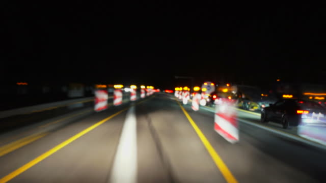 car passing a construction zone night s tlhot - roadworks stock videos & royalty-free footage