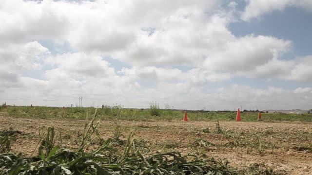 car passing cones in an open field - 固定撮影点の映像素材/bロール