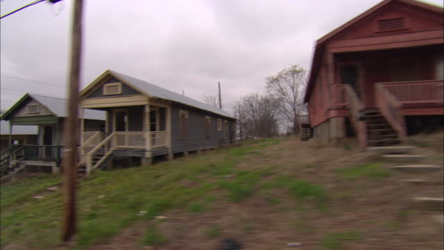 side pov, car passing row of slum houses, shreveport, louisiana, usa - slum stock-videos und b-roll-filmmaterial