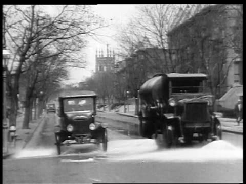 B/W 1927 car passing street cleaning truck on city street / educational