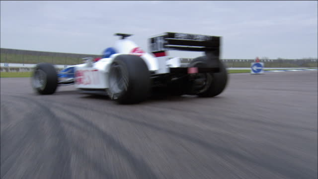 Car point of view chasing Formula One race car around track