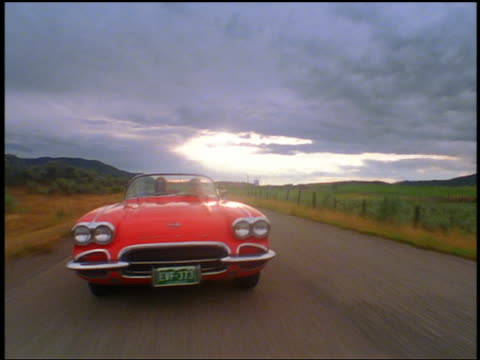 rear car point of view couple driving on country road in 1961 corvette + passing camera with woman blowing kiss - classic car stock videos and b-roll footage