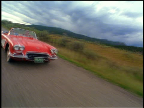 REAR car point of view couple driving on country road in 1961 Corvette with woman blowing kiss
