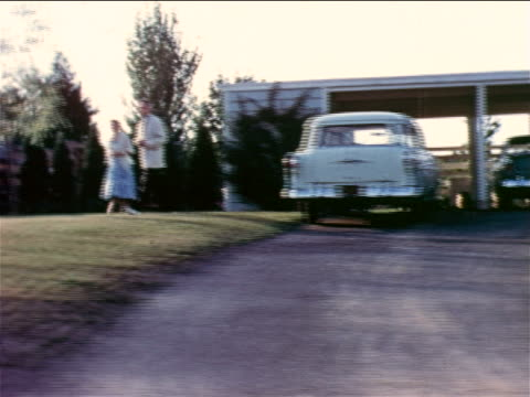 1957 car point of view couple walking on lawn by driveway / educational
