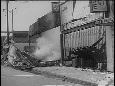 B/W 1965 car point of view destroyed buildings on city street after Watts race riots Los Angeles / newsreel