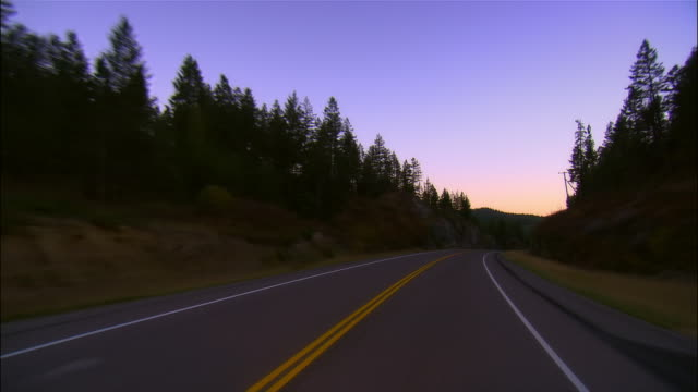 car point of view driving along empty highway outside small town at dusk / montana - empty road stock videos & royalty-free footage