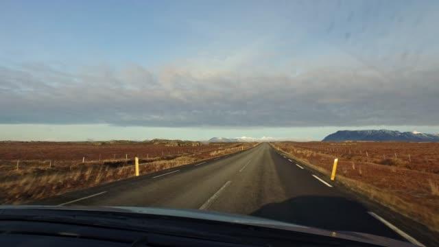 vídeos de stock e filmes b-roll de ws car point of view driving along sunny remote road,iceland - para brisas