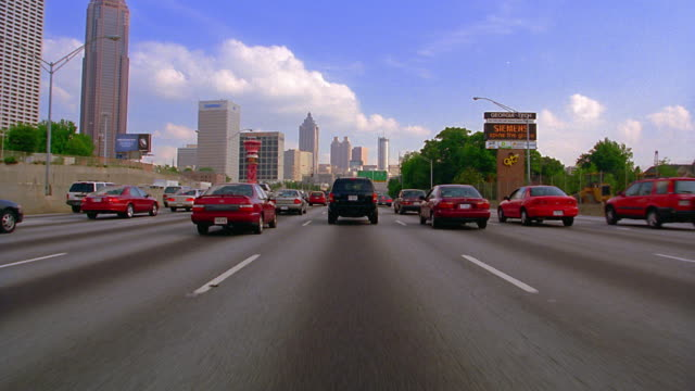 car point of view driving in traffic on highway with atlanta skyline in background / georgia - georgia stati uniti meridionali video stock e b–roll