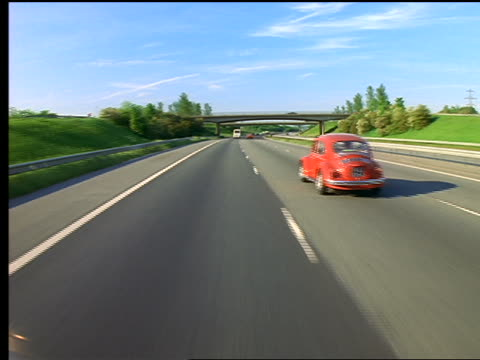 Car point of view driving on 3-lane highway behind red Volkswagen Beetle / England