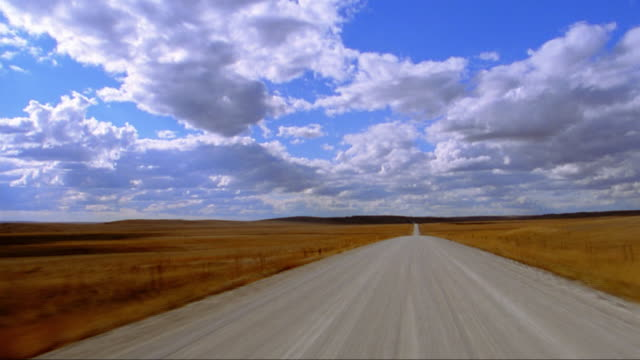 Car point of view driving on dirt road surrounded by grassland / Sand Hills, Nebraska