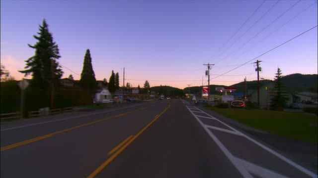 car point of view driving on highway through small town at dusk / montana - ガソリンスタンド点の映像素材/bロール