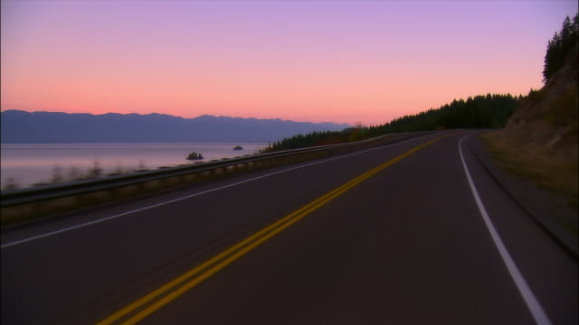 car point of view driving past flathead lake at sunset / montana - flathead lake stock videos and b-roll footage