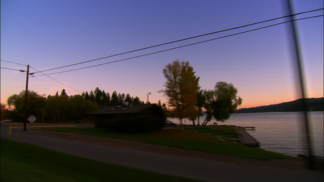 car point of view driving shore of flathead lake at sunset / montana - flathead lake stock videos and b-roll footage