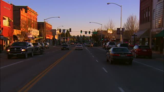 Car point of view driving south through green lights on Main Street at dusk / Kalispell, Montana