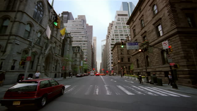 Car point of view driving up Madison Avenue between 50th and 51st streets in midtown Manhattan / New York City