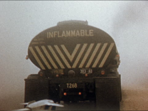 1954 car point of view driving up to oil truck with 'Inflammable' printed on rear on foggy day / USA