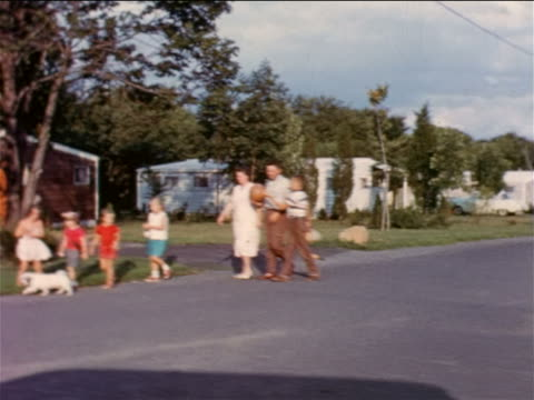 1957 car point of view family walking with dog along suburban road / educational