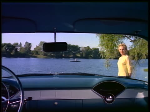 stockvideo's en b-roll-footage met 1955 car point of view pan from back seat of woman walking past car with lake in background / commercial - 1955