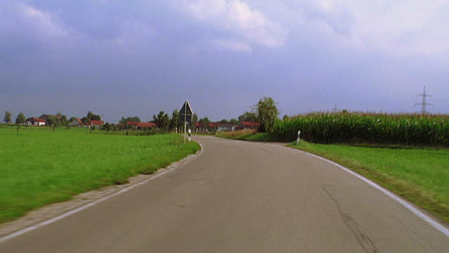 Car point of view  PAN from field to road through countryside with farms + houses / Bavaria, Germany