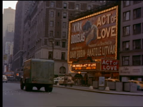 1953 rear car point of view in traffic on broadway past movie theaters + stores / new york city - broadway manhattan stock-videos und b-roll-filmmaterial