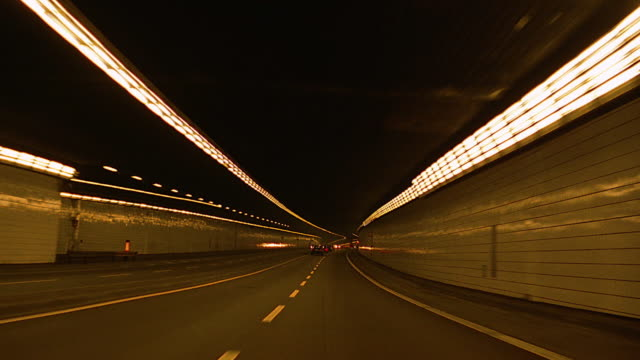 vidéos et rushes de car point of view in traffic on highway lined by trees / through tunnel / munich, germany - tunnel