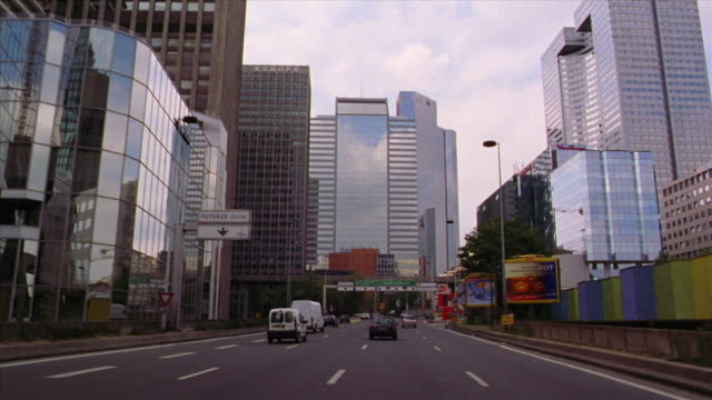Car point of view PAN in traffic on highway past skyscrapers + office buildings in La Defense area / Paris