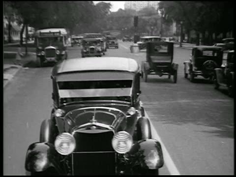 stockvideo's en b-roll-footage met b/w 1928 rear car point of view lincoln car driving on suburban street / detroit, michigan / newsreel - 1928