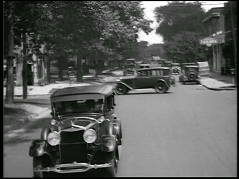 b/w 1928 rear car point of view lincoln car driving on suburban street / detroit, michigan / newsreel - bewegliches hintergrundbild stock-videos und b-roll-filmmaterial