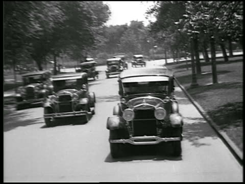 B/W 1928 REAR car point of view Lincoln car overtaking others on suburban street / Detroit, Michigan / news.