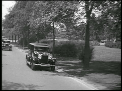b/w 1928 rear car point of view lincoln car passing on street / detroit, michigan / newsreel - 1928 stock videos & royalty-free footage