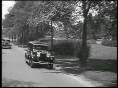 stockvideo's en b-roll-footage met b/w 1928 rear car point of view lincoln car passing on street / detroit, michigan / newsreel - 1928