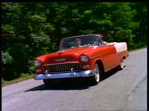 vídeos de stock e filmes b-roll de 1955 rear car point of view of couple driving red + white convertible chevrolet bel air on country road - general motors