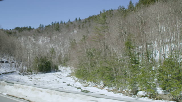 car point of view of mountain road passing by forest and frozen river during winter - winter点の映像素材/bロール