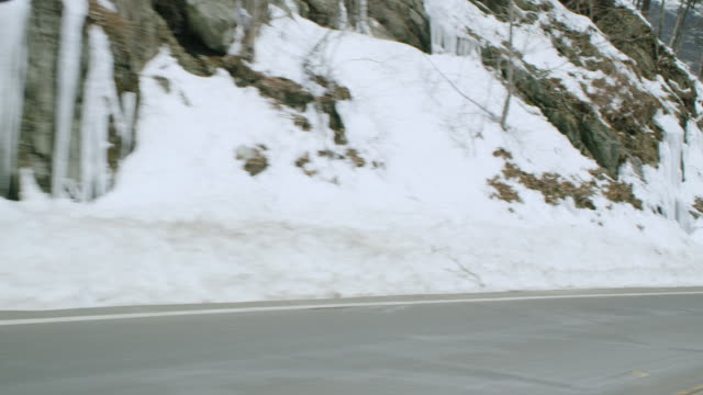 car point of view of mountain road passing snow covered rocks during winter - winter点の映像素材/bロール
